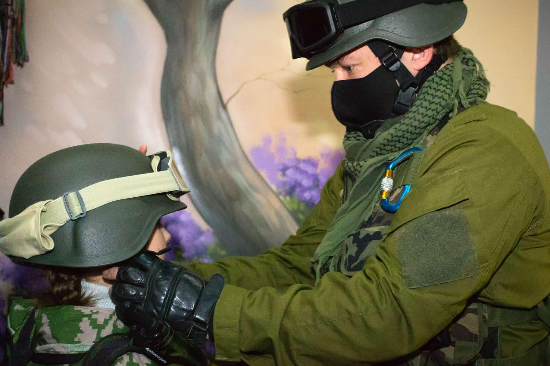 ребёнка одевают в военную форму на фотозоне