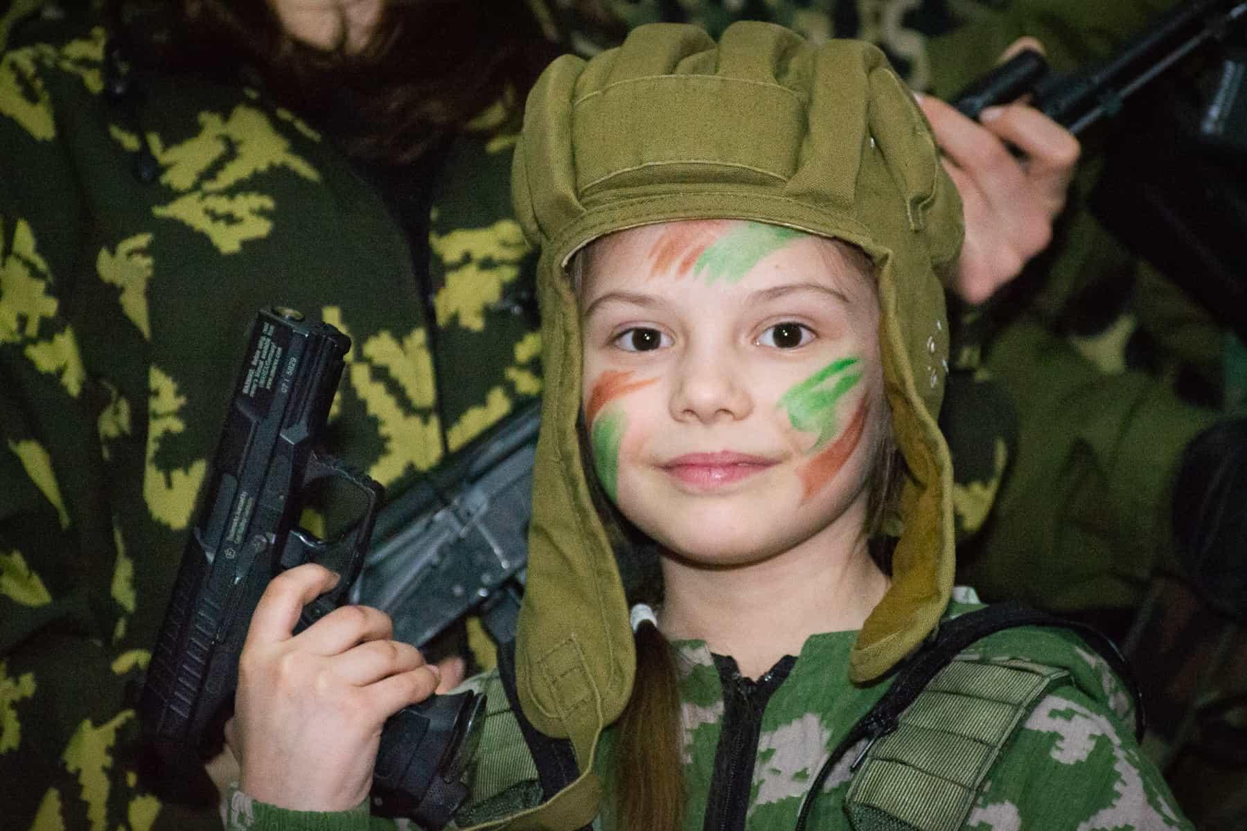 Ребёнок в маскировочном гриме на фотозоне милитари